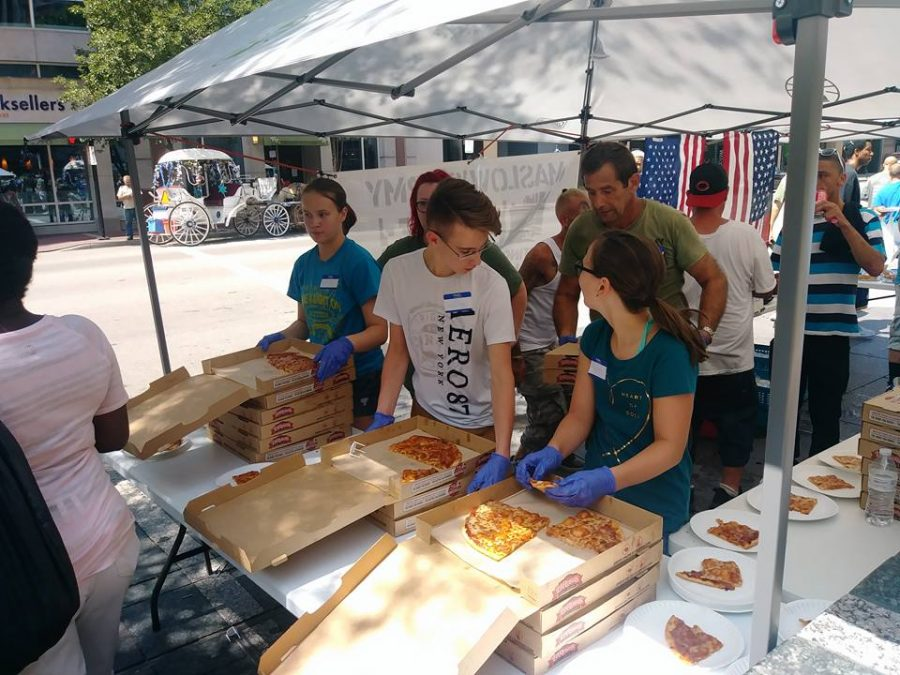 Volunteers help Maslows Army distribute pizza on Fountain Square
