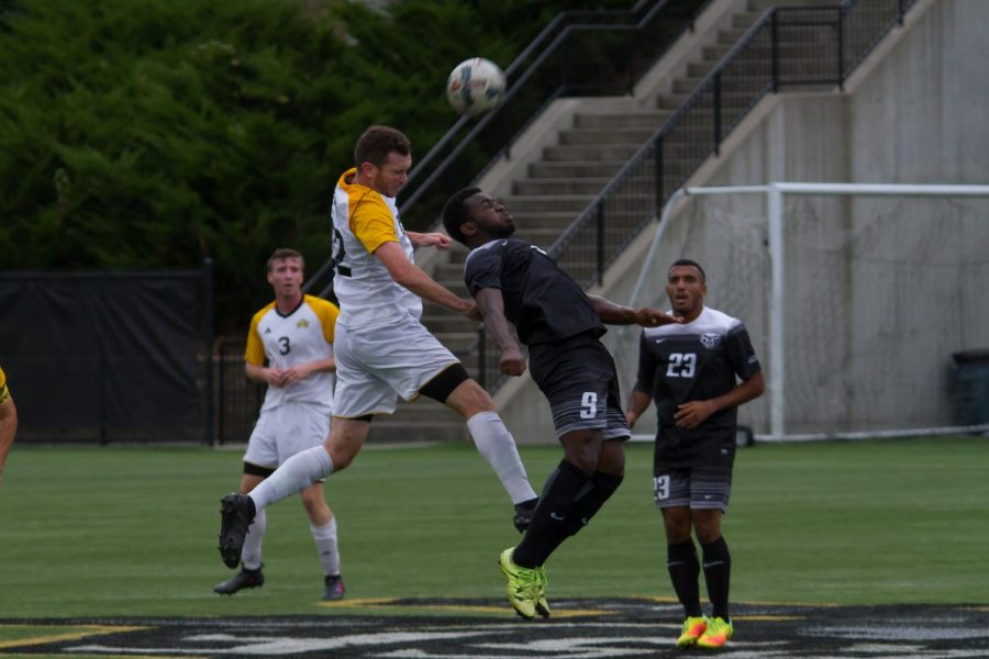 Liam Evans (22) goes up for a head in the game against Oakland