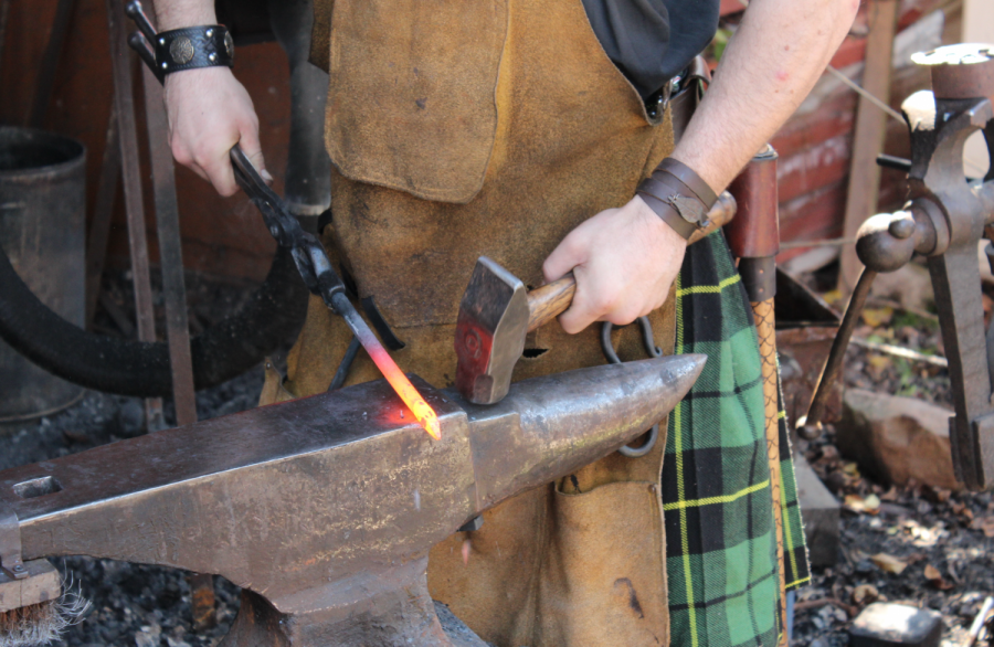 A blacksmith at the Dragon's Forge shapes red-hot metal with a hammer and anvil.