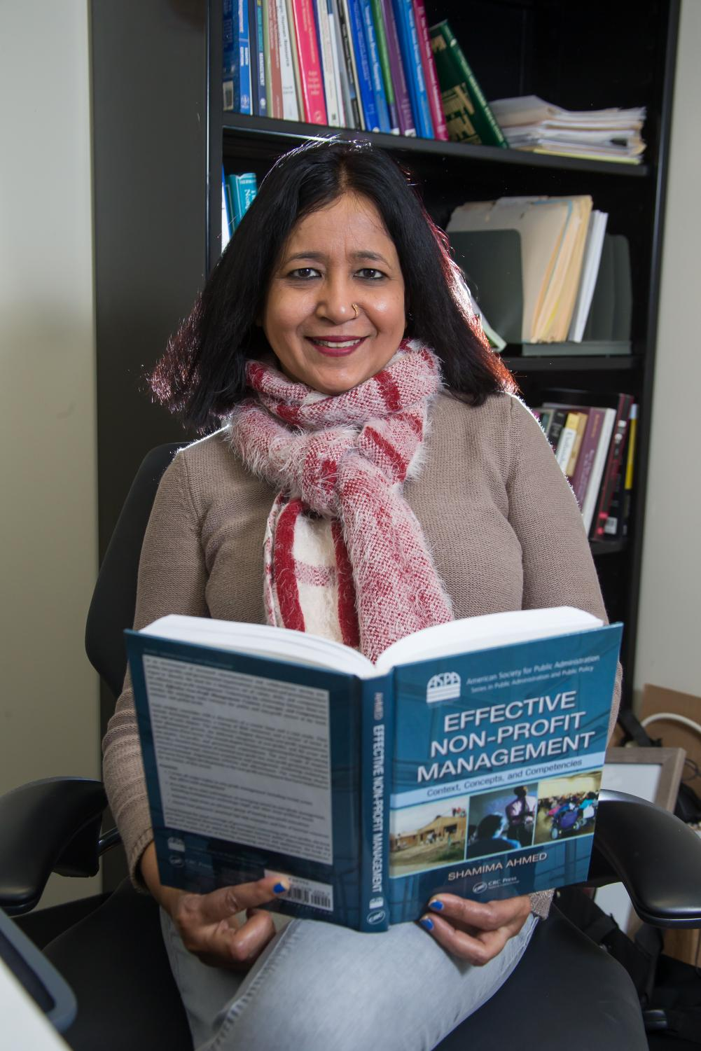 Ahmed, new member of the Fulbright Specialist program, sits with one of her published works