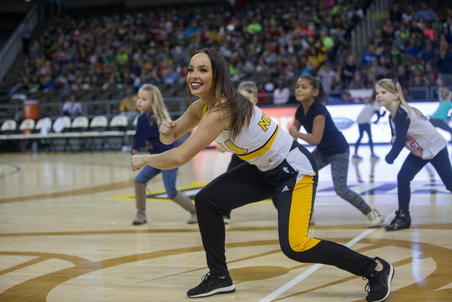 A+member+of+the+NKU+dance+team+leads+fans+in+a+dance+at+halftime.