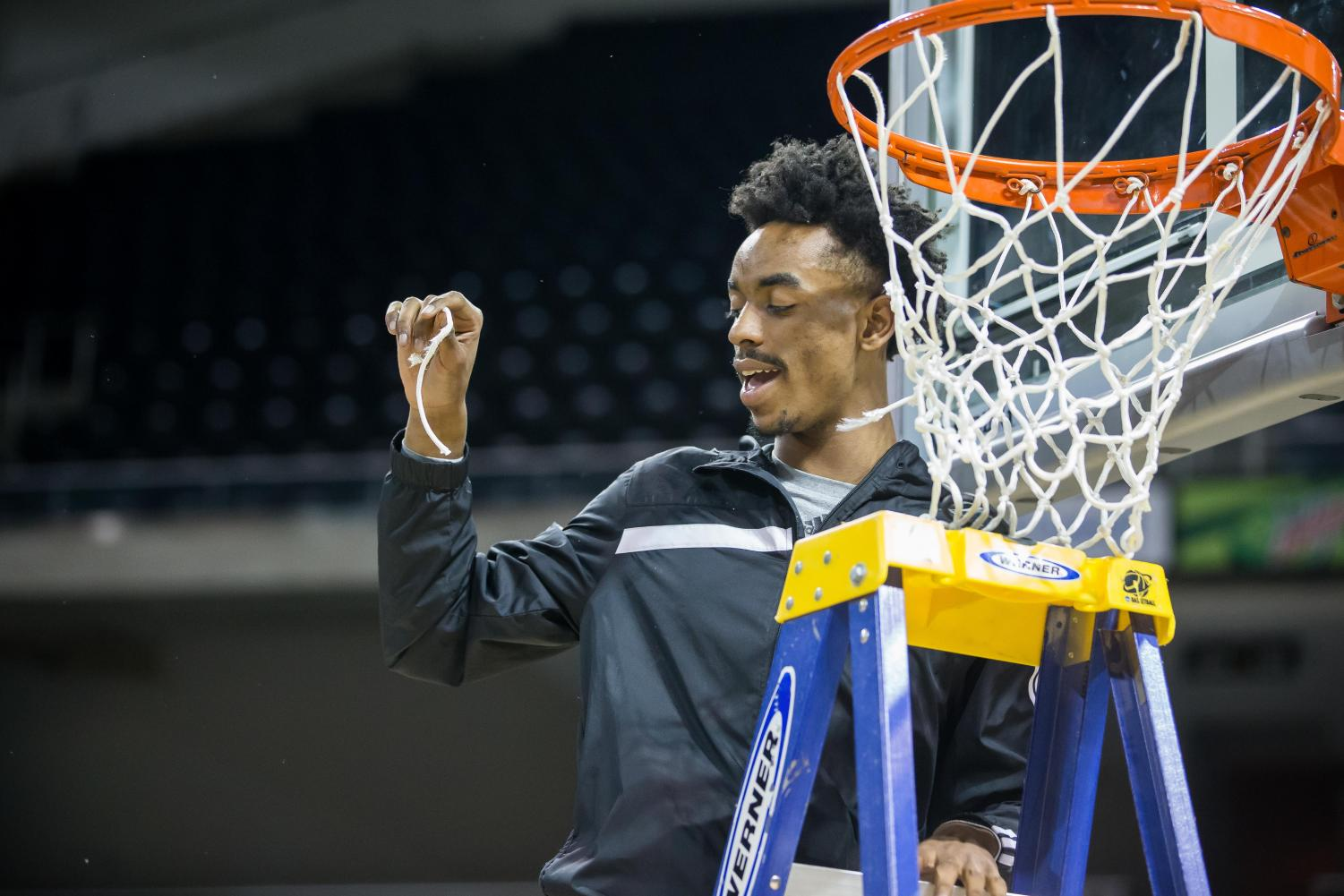 Jalen Tate (5) shows off his piece of the net after the men secured 1st place in the Horizon League.