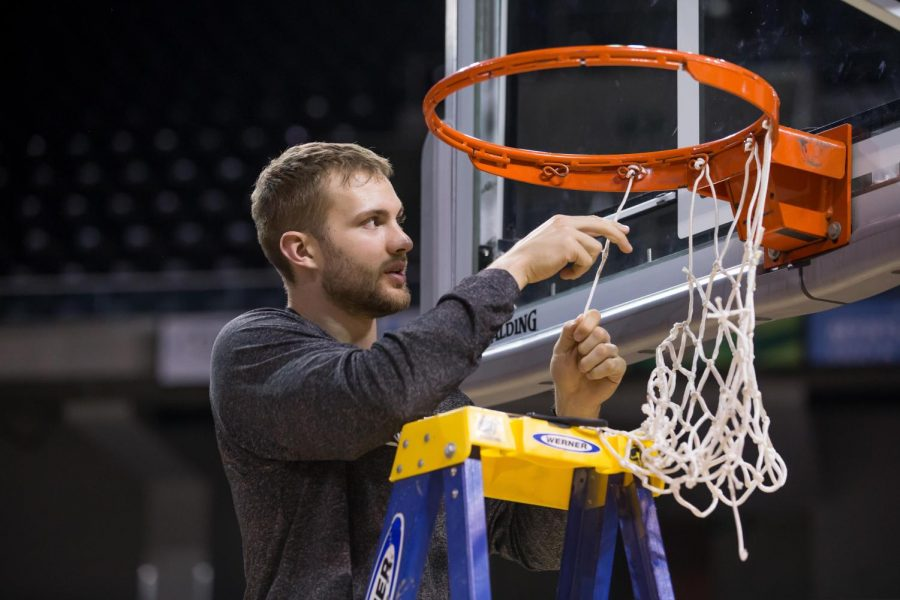 Carson Williams (23) cuts off his section of the net after securing 1st place in the Horizon League.