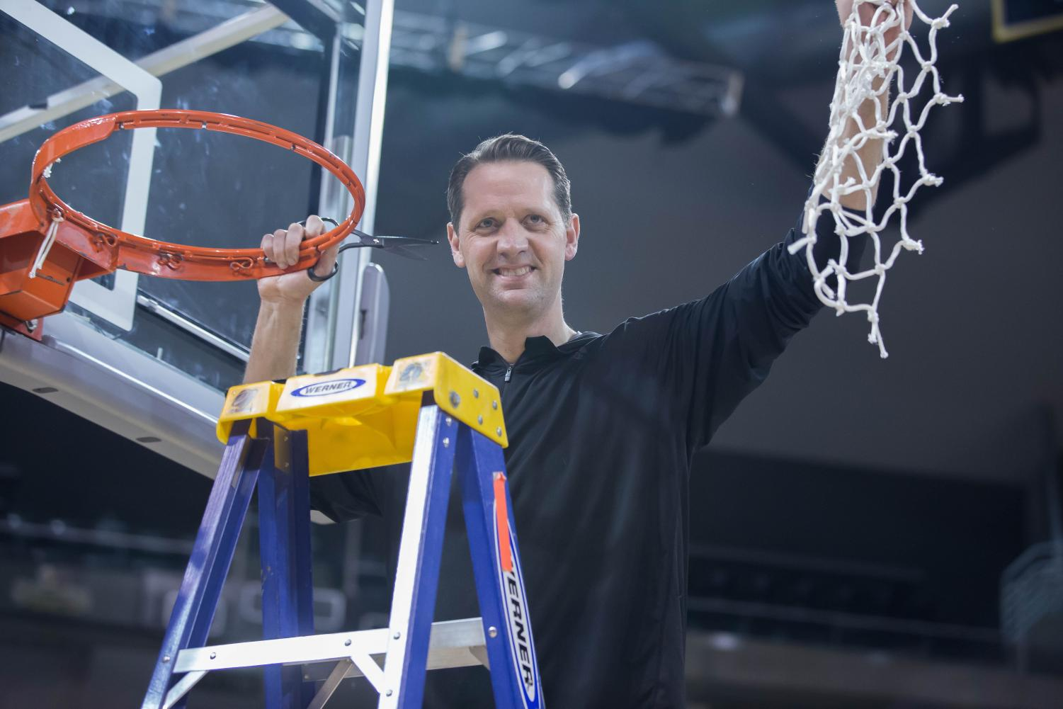 Head Coach John Brannen holds up the net to the spectators in BB&T Arena.