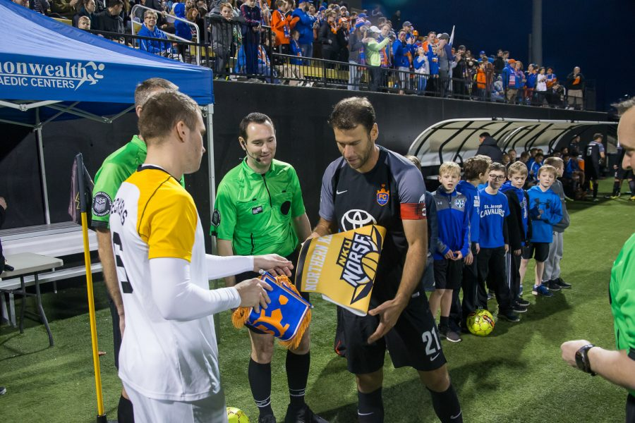 Bastian Beckers (6) exchanges flags with a the FC Cincinnati captain before the game.