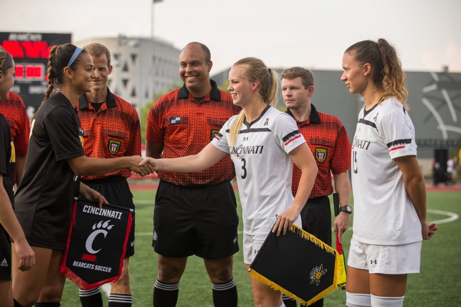 Samantha+Duwel+%2827%29+shakes+hands+with+UC+captains+during+the+pre-game+banner+exchange.