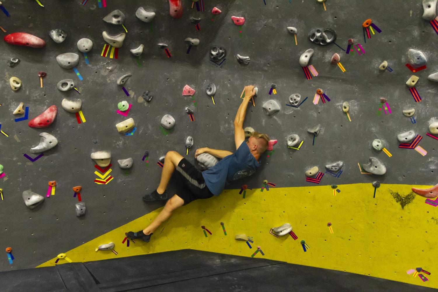 James Blazina attempts a challenging climbs route on the Campus Recreation Center's bouldering wall.