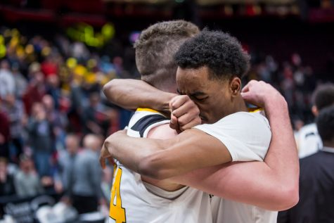 Jalen Tate (11) hugs Drew McDonald (34) after his game winning three point shot during the semi-final game of the Horizon League Tournament. The ball was inbounded with 9 seconds on the clock.