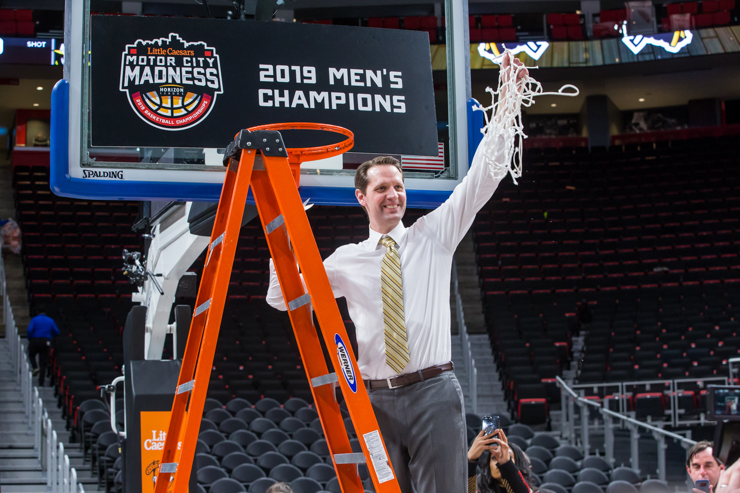 Men's Basketball Head Coach John Brannen holds up the net following the final game of the Horizon League Tournament. The Norse defeated Wright State 77-66.