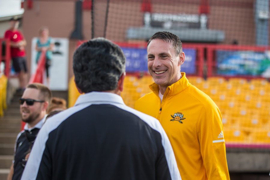 Men's Basketball Head Coach Darrin Horn (right) talks with NKU President Ashish Vaidya (left) prior to the first pitch at the Florence Freedom Baseball Game.