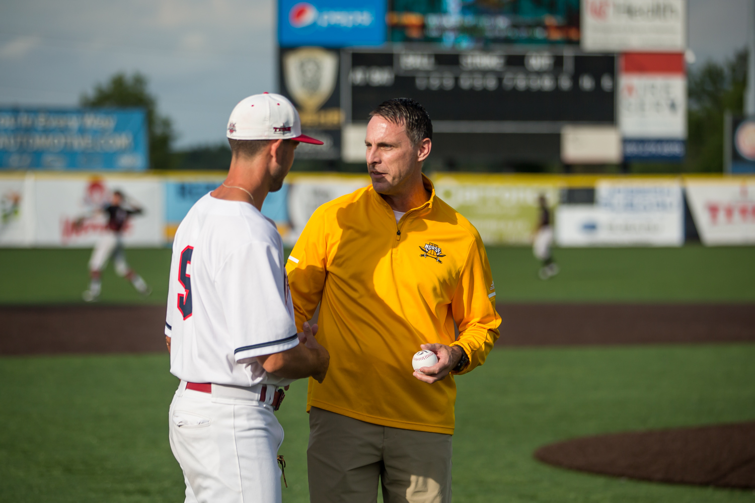 Men%27s+Basketball+Head+Coach+Darrin+Horn+receives+the+first+pitch+ball+from+a+Florence+Freedom+player.