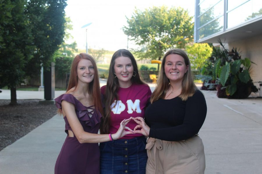 Brianna Collins, Rachel Henry, Gabby Manley pose with the Phi Mu hand sign.
