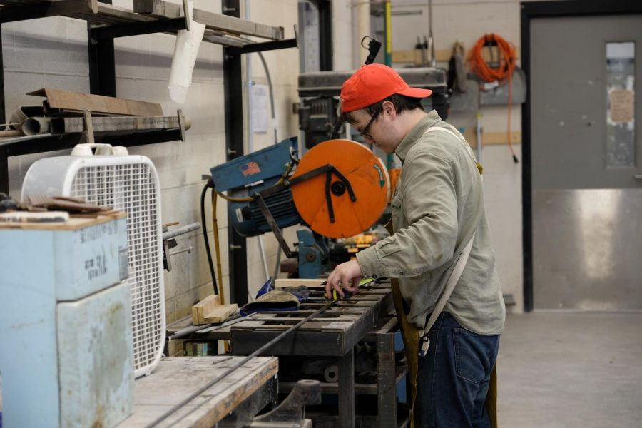 New media art major Zack Hargrove cuts away at a piece of metal for use in Light Streams.