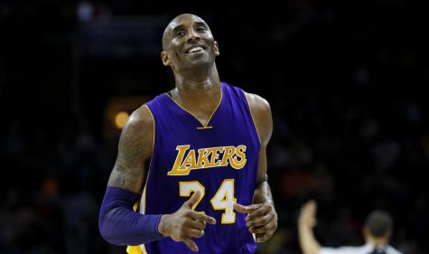 Los Angeles Lakers' Kobe Bryant smiles as he jogs to the bench during the first half of an NBA basketball game against the Philadelphia 76ers, Tuesday, Dec. 1, 2015, in Philadelphia. AP Photo by Matt Slocum.