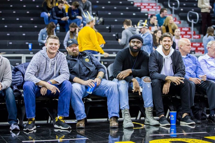 Mens Basketball Alum sit court-side at a basketball game.