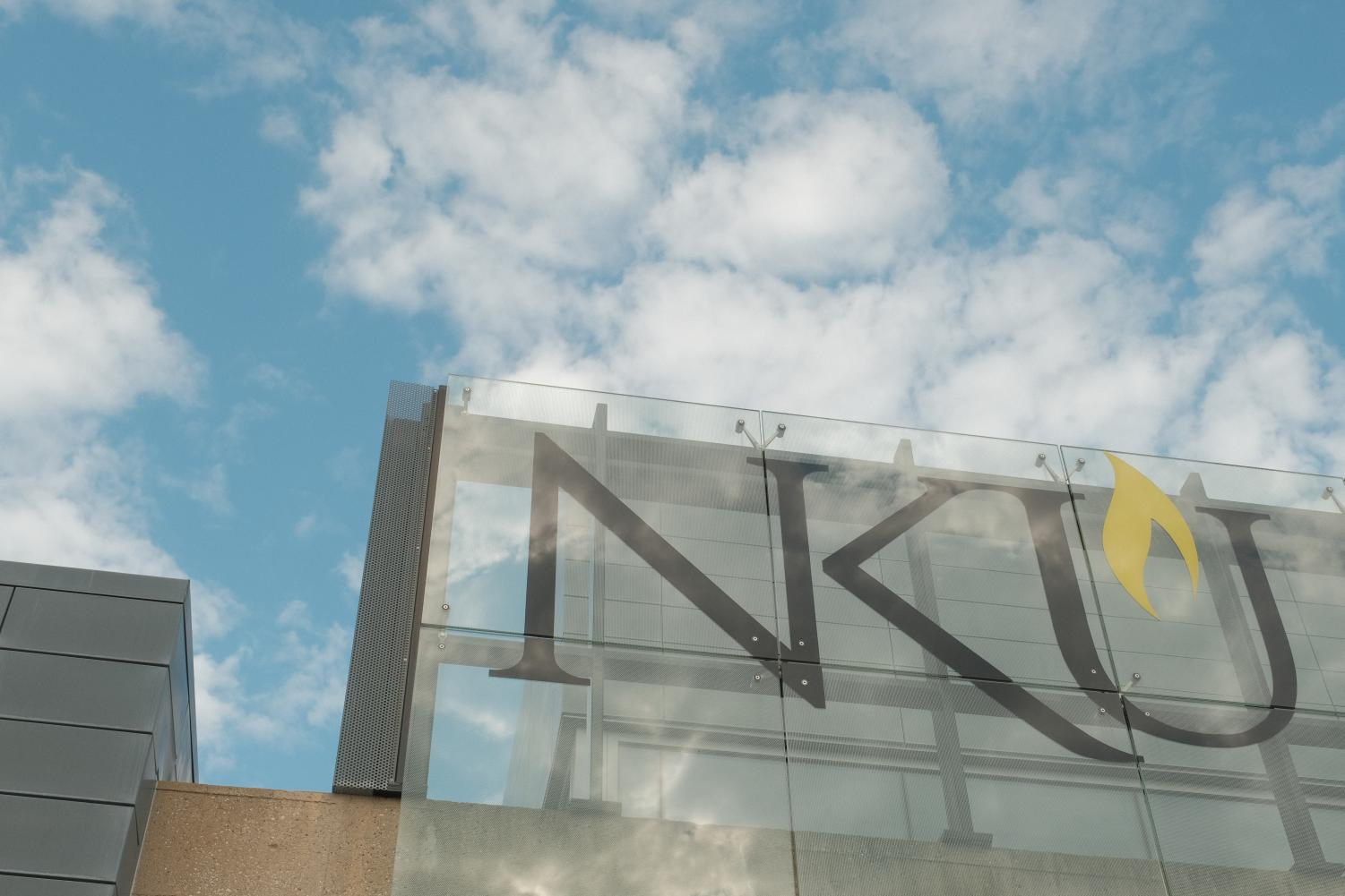 A sign that, in black text, says NKU. Clouds are in the sky.