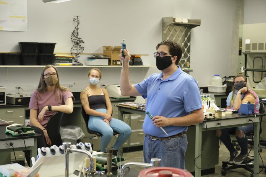 Assistant Professor Brian Carlson goes over a mock pipette demonstration with the class.