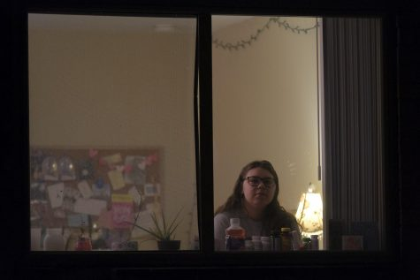 Sleczkowski sits in her apartment. She stares out through the window.