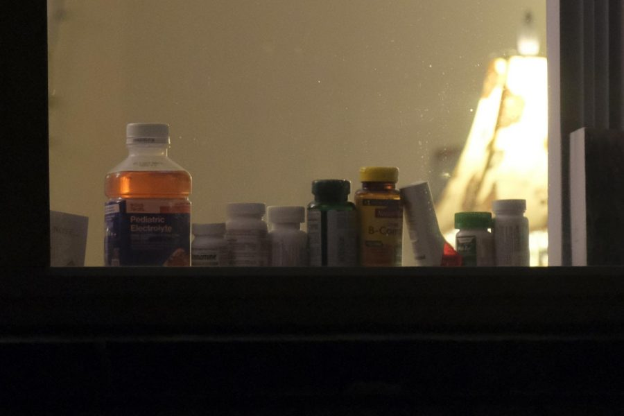 Various pill and vitamin bottles line a window.
