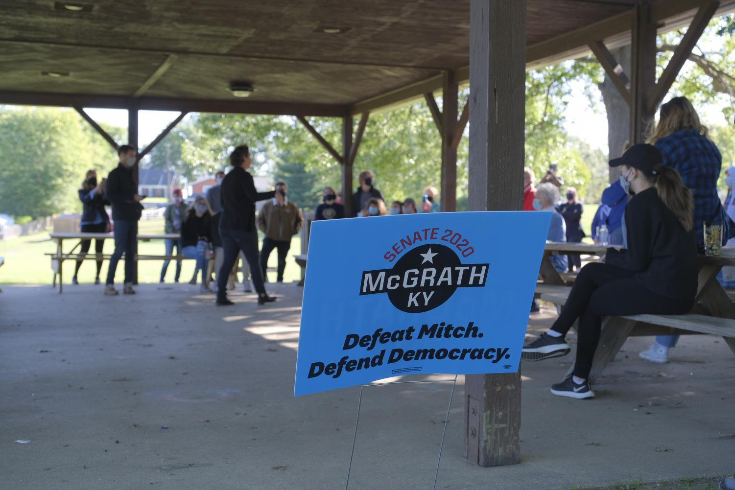 """A blue campaign sign says """"Defeat Mitch. Defend Democracy."""""""
