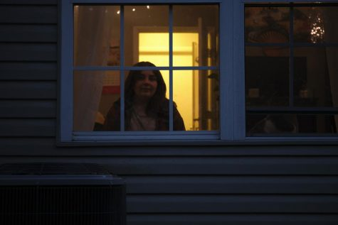Bailey Fox sits inside her apartment through the bedroom window.