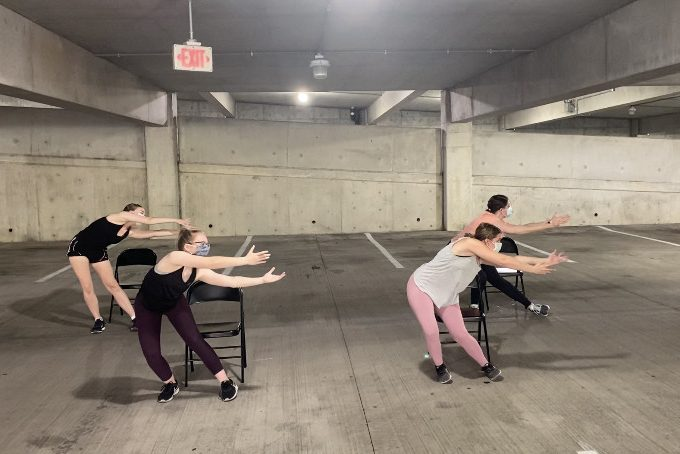 Four dancers rehearse in a parking garage.