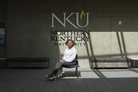 Kaitlin Minniefield sits on a chair in front of an NKU logo. She's wearing a white shirt and black pants.