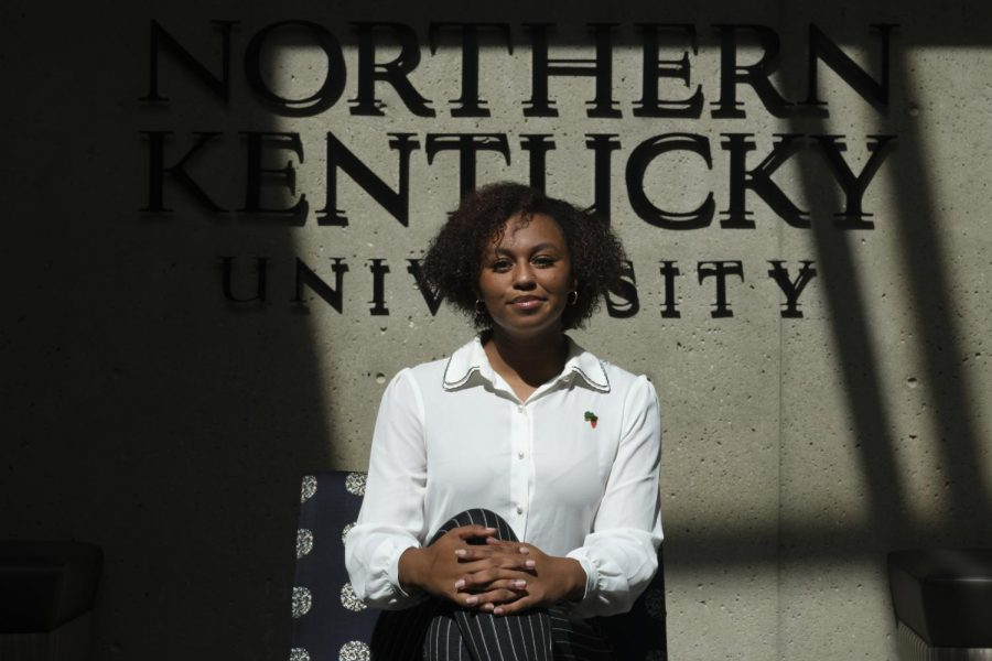 Kaitlin Minniefield sits on a chair in front of an NKU sign. She's wearing a white shirt with black dress pants. Her hands are crossed on her lap.