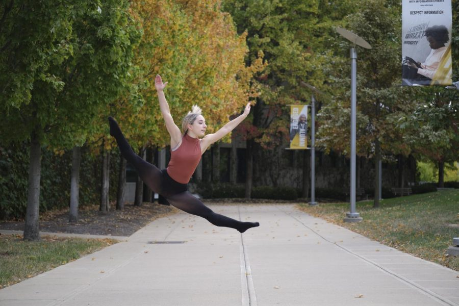 Brianna Mullins jumps in the air wearing a pink leotard and black leggings. There are colorful autumn trees behind her.