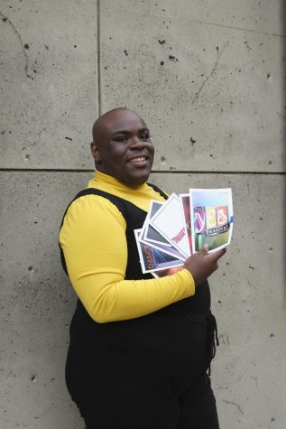 Je'Shaun Jackson wears a yellow shirt with a black romper over it. He's carrying theatre playbills and smiling.