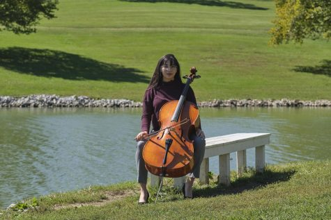 Gita Srinivasan sits on a park bench in front of a lake with her cello. She