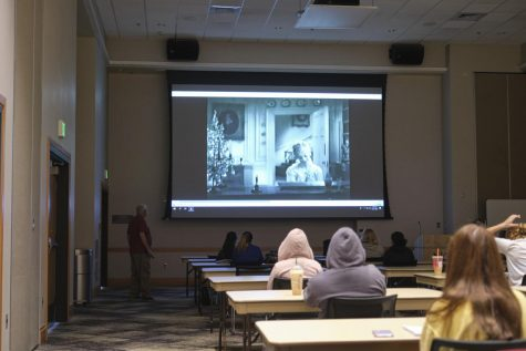 Socially distanced students watch a movie in the Student Union ballroom.