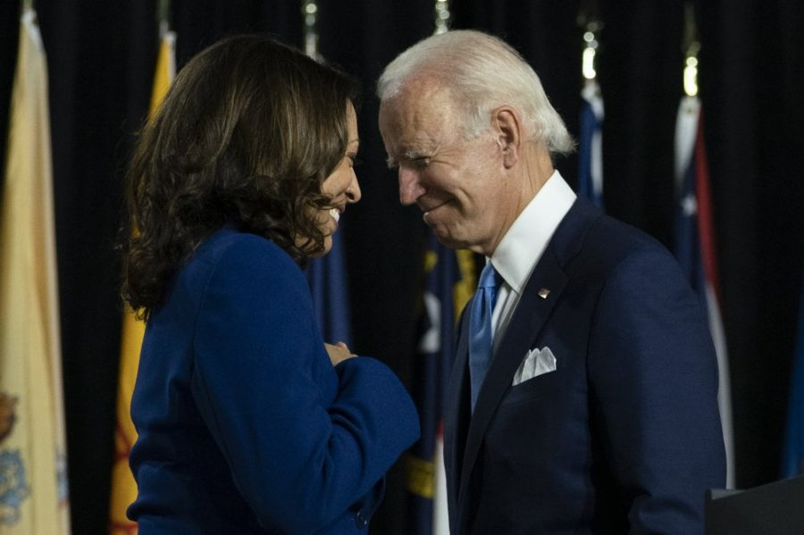 In this Aug. 12, 2020, Democratic presidential candidate former Vice President Joe Biden and his running mate Sen. Kamala Harris, D-Calif., pass each other as Harris moves to the podium to speak during a campaign event.
