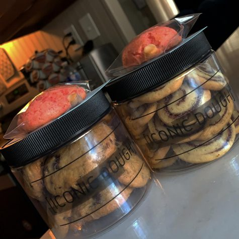 Two jars of cookies filled with chocolate chip, cinnamon roll and more.