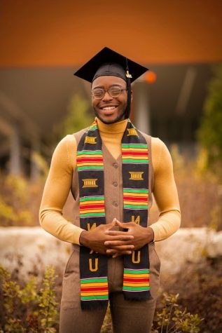 Jontay Brown is standing, smiling, wearing bright colors such as yellow, red and green on a graduation sash. He also is wearing a black graduation cap.