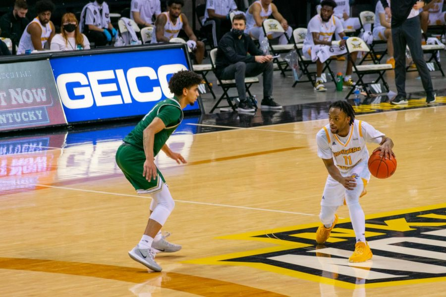 NKU guard Bryson Langdon (11) dribbles at the top of the key. Langdon finished with 15 points.