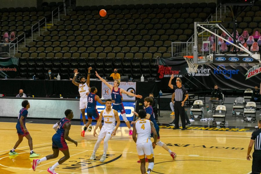 Trevon Faulkner (12) shoots a three over two Detroit Mercy defenders in the Horizon League Tournament quarterfinals.