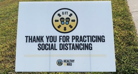 """Thank you for practicing social distancing"" sign in front of the Rec Center on campus in the grass."