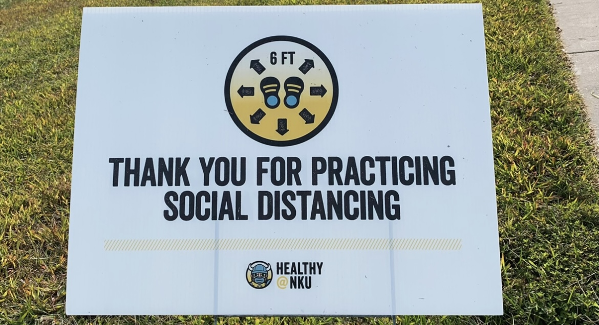 """""""Thank you for practicing social distancing"""" sign in front of the Rec Center on campus in the grass."""