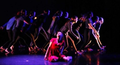 A girl in a red dress sitting on the stage floor with dancers behind her in the shadows.