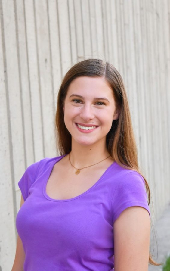 Alyssa Taylor standing wearing a purple shirt smiling at the camera.