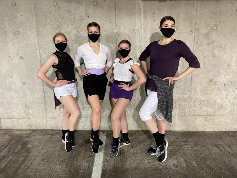Four dancers wearing face masks and popping their leg up.