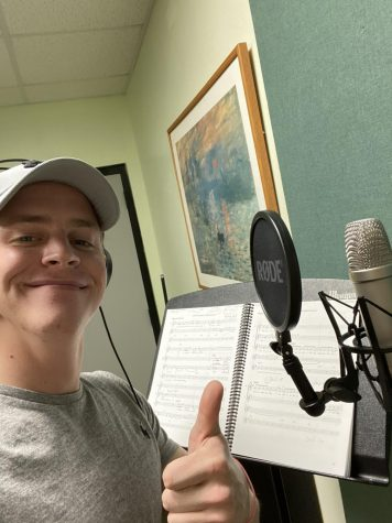 Jackson holding a thumbs up and smiling in front of a recording microphone.