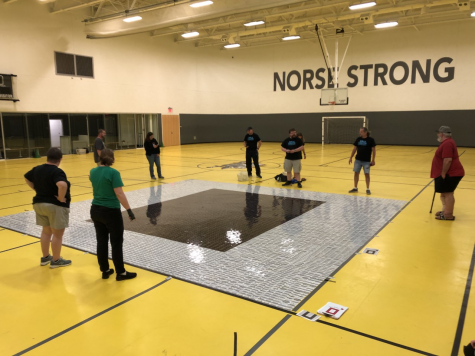 Sean Gardner, Shawn Reed, Paul Phillipy and others stand in a circle and create a massive 0 out of plastic gift cards at the NKU Campus Rec Center.