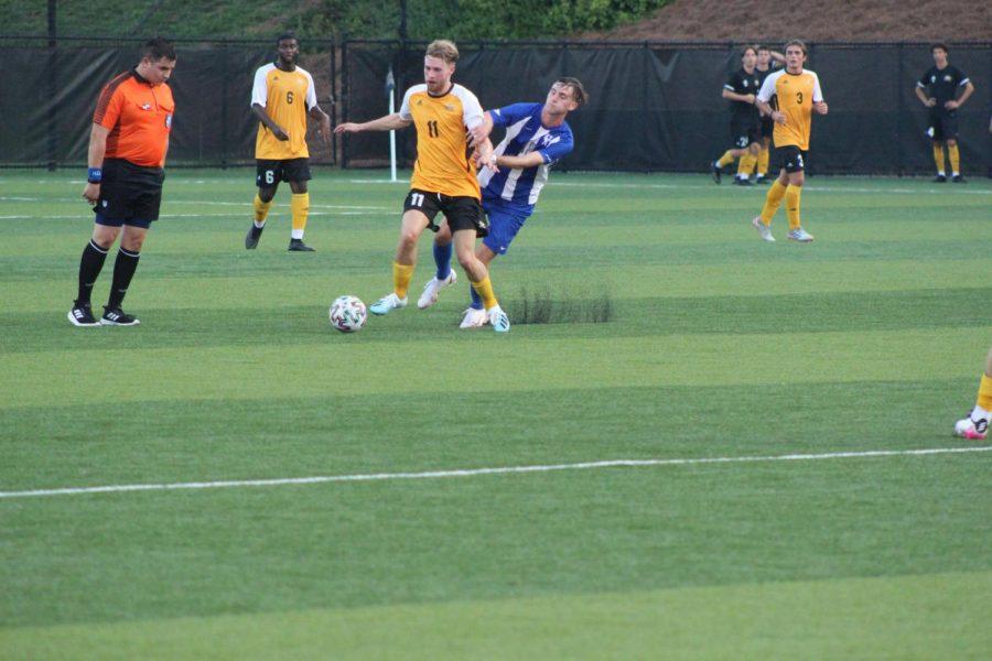 NKU freshman midfielder Gustav Severinsen (11) dribbles through contact during NKUs 2-0 loss against Kentucky on Friday night.