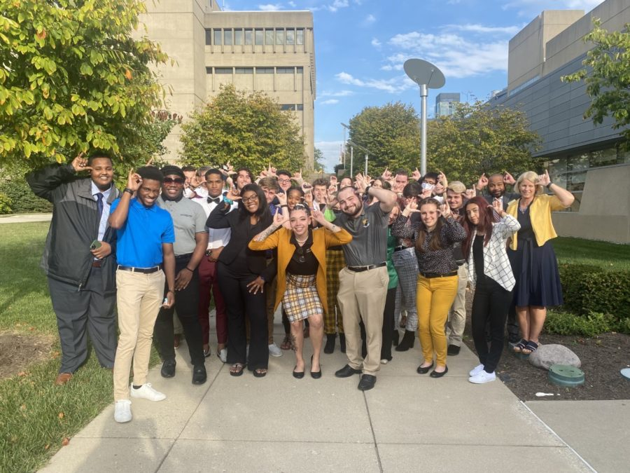 SGA members next to the SU after Mondays meeting. A large group of almost 30 members all doing the Norse up motion with their hands next to their heads.