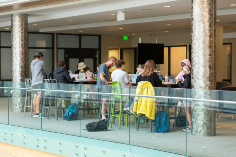 Students conversing with one another in the Student Union sitting at tables.