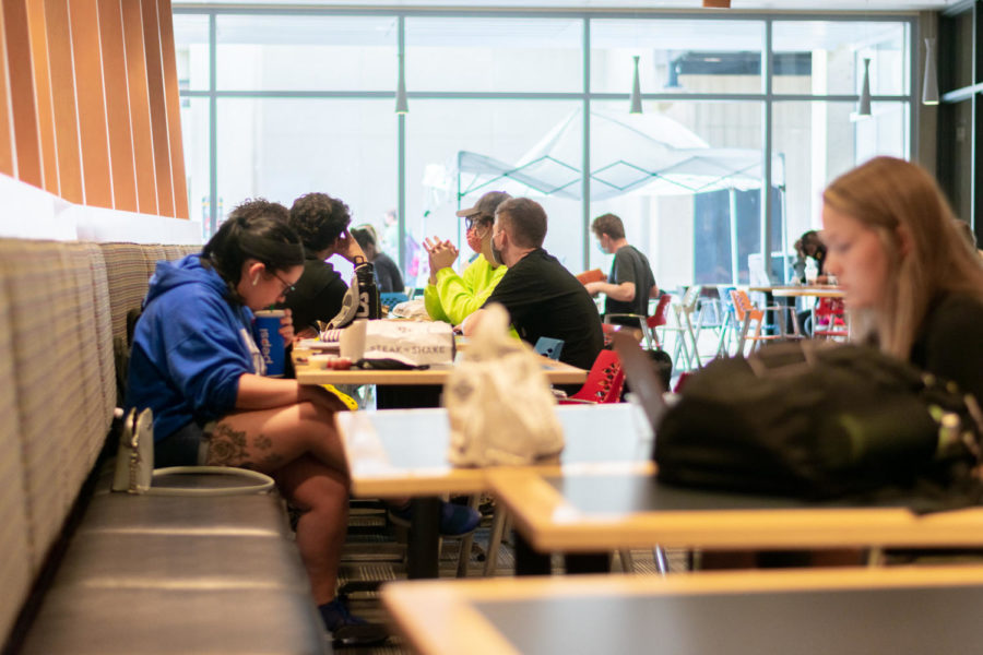 Students eating and talking to one another in the Student Union at tables spread out.