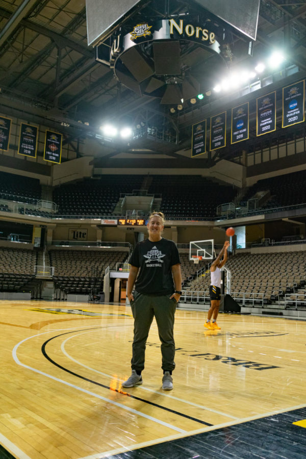 Molly Glick poses for a picture on the court at BB&T Arena. Glick is preparing for her first season as womens basketball Director of Operations.